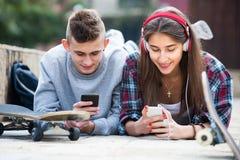 Amigos que se relajan con los teléfonos móviles Foto de archivo