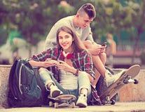Amigos que se relajan con los teléfonos móviles Fotografía de archivo