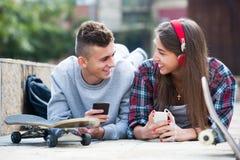 Amigos que se relajan con los teléfonos móviles Imagenes de archivo