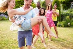 Amigos que se relajan en jardín del verano junto Imagen de archivo