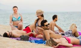 Amigos que se relajan en la playa arenosa Foto de archivo