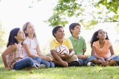 Amigos que se sientan al aire libre con el balón de fútbol Foto de archivo libre de regalías