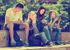 Amigos que se sientan con los teléfonos móviles en parque Imagen de archivo