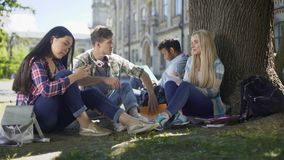 Amigos que se sientan debajo de árbol, usando los teléfonos, hablando el uno al otro, comunicación almacen de video