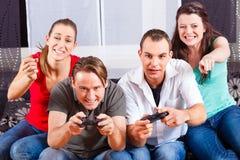 Amigos que se sientan delante de la caja de la videoconsola Fotos de archivo
