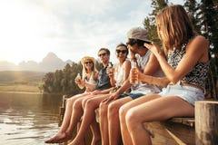 Amigos que se sientan en el embarcadero en las cervezas de consumición del lago foto de archivo
