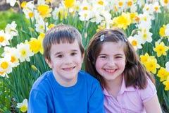 Amigos que se sientan en flores fotografía de archivo libre de regalías