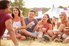 Amigos que se sientan en hierba y que comen en el festival de música fotos de archivo libres de regalías