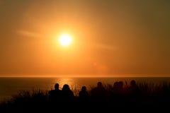 Amigos que se sientan en la duna en puesta del sol Imagen de archivo