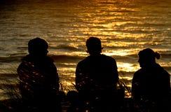 Amigos que se sientan en la duna en puesta del sol Fotos de archivo