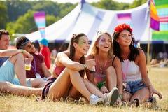 Amigos que se sientan en la hierba que mira un carruaje en un festival de música Fotografía de archivo