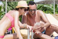 Amigos que se sientan en la playa, divirtiéndose con un teléfono Imagen de archivo libre de regalías