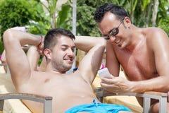 Amigos que se sientan en la playa, divirtiéndose con un teléfono Foto de archivo libre de regalías