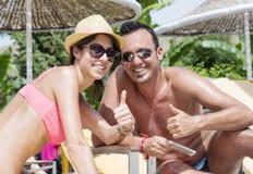 Amigos que se sientan en la playa, divirtiéndose con un teléfono Imagen de archivo
