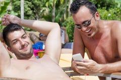 Amigos que se sientan en la playa, divirtiéndose con un teléfono Fotos de archivo libres de regalías