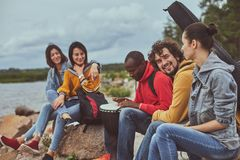 Amigos que se sientan en la playa y que escuchan la música foto de archivo