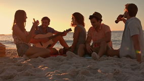 Amigos que se sientan en la playa y que tocan la guitarra almacen de metraje de vídeo