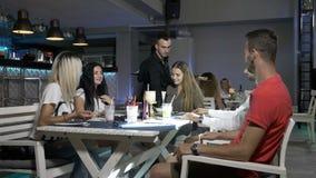 Amigos que se sientan en la tabla y los cócteles de consumición que son servidos por los cocineros con los platos de la comida en metrajes