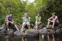 Amigos que se sientan en piedras de Forest River Fotografía de archivo