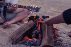 Amigos que se sientan en piedras en la playa El hombre está tocando la guitarra Fotografía de archivo