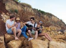Amigos que se sientan en piedras en la playa El hombre está tocando la guitarra Foto de archivo libre de regalías