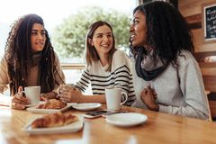 Amigos que se sientan en un café y hablar fotografía de archivo