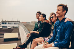 Amigos que se sientan junto en tejado fotografía de archivo