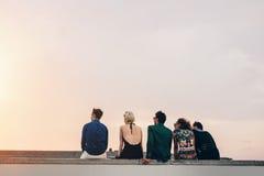 Amigos que se sientan junto en tejado en la puesta del sol fotos de archivo