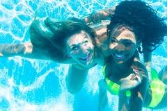 Amigos que se zambullen bajo el agua en piscina Foto de archivo libre de regalías