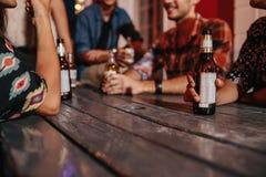 Amigos que sentam-se em torno de uma tabela que tem bebidas Imagens de Stock