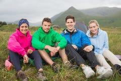 Amigos que sentam-se fora em uma viagem de acampamento Fotografia de Stock Royalty Free