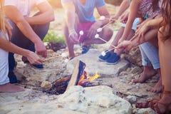 Amigos que sentam-se na areia na praia no círculo com marshmal foto de stock royalty free