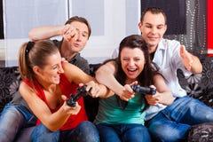 Amigos que sentam-se na frente da caixa do console do jogo Imagens de Stock Royalty Free