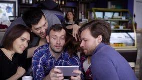 Amigos que sentam-se na tabela no café que passa junto o tempo de lazer junto e que usa o dispositivo digital Três consideráveis filme
