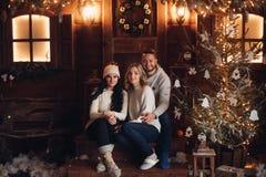 Amigos que sentam-se no patamar na sala decorada Natal fotos de stock royalty free