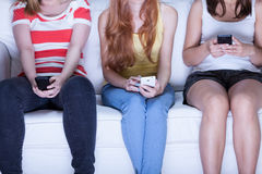 Amigos que sentam-se no sofá e que usam telefones Fotografia de Stock Royalty Free