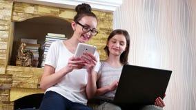 Amigos que socializan en casa y que juegan a juegos en el ordenador portátil y la tableta, muchachas que se sientan junto metrajes