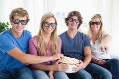 Amigos que sonríen como comen las palomitas y miran una película 3d Fotografía de archivo