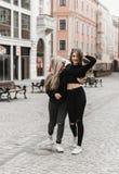 Amigos que sonr?en y que caminan en la ciudad vieja fotografía de archivo