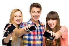 Amigos que sostienen los teléfonos móviles Fotos de archivo