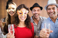 Amigos que sostienen los vidrios del champán que se ríen de la cámara Fotos de archivo libres de regalías