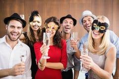 Amigos que sostienen los vidrios del champán que se ríen de la cámara Foto de archivo libre de regalías