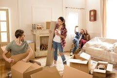 Amigos que têm o divertimento e que abrem caixas na casa nova Imagens de Stock Royalty Free