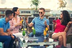 Amigos que têm o divertimento e que bebem os cocktail exteriores imagem de stock royalty free