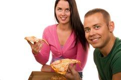 Amigos que têm o divertimento e que comem a pizza Imagem de Stock