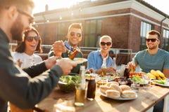 Amigos que têm o jantar ou o partido do BBQ no telhado imagem de stock royalty free