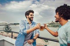 Amigos que têm o partido na cerveja bebendo do telhado imagens de stock