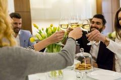 Amigos que têm uma refeição na mesa de jantar e no brinde com vinho branco imagem de stock royalty free