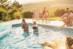 Amigos que t?m o divertimento em um partido da piscina foto de stock royalty free