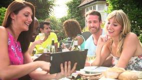 Amigos que tienen barbacoa en casa que mira la tableta de Digitaces metrajes